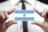 Businessman holding a business card with Argentina Flag — Stock Photo