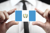 Businessman holding a business card with Guatemala Flag — Stock Photo