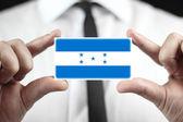 Businessman holding a business card with Honduras Flag — Stock Photo
