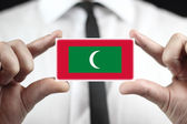 Businessman holding a business card with Maldives Flag — Stock fotografie