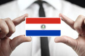 Businessman holding a business card with Paraguay Flag — Stock Photo