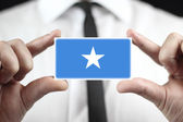 Businessman holding a business card with Somalia Flag — Stock fotografie