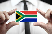 Businessman holding a business card with South Africa Flag — Stock fotografie