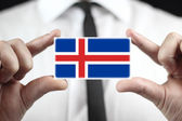 Businessman holding a business card with Iceland Flag — Stock fotografie