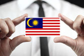 Businessman holding a business card with Malaysia Flag — Stock fotografie