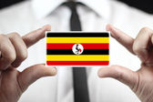 Businessman holding a business card with Uganda Flag — Stock fotografie