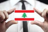 Businessman holding a business card with Lebanon Flag — Stock fotografie