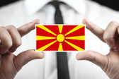 Businessman holding a business card with Macedonia Flag — Stock fotografie