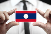 Businessman holding a business card with Laos Flag — Stock fotografie