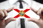 Businessman holding a business card with Florida Flag — Stock fotografie