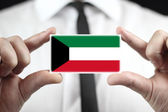 Businessman holding a business card with Kuwait Flag — Stok fotoğraf