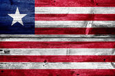 Liberia Flag painted on old wood plank texture — Stock Photo