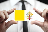 Businessman holding a business card with Vatican City Flag — Stock Photo