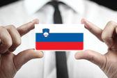 Businessman holding a business card with Slovenia Flag — Stockfoto