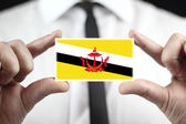 Businessman holding a business card with Brunei Flag — Stock Photo