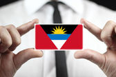 Businessman holding a business card with Antigua and Barbuda Flag — Stock Photo