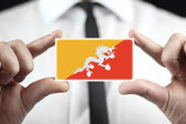 Businessman holding a business card with Bhutan Flag — Stock Photo