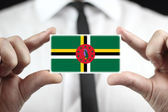 Businessman holding a business card with Dominica Flag — Stock Photo