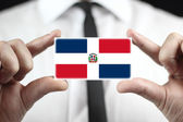 Businessman holding a business card with Dominican Republic Flag — Stock Photo