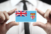 Businessman holding a business card with Fiji Flag — Stock Photo