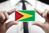 Businessman holding a business card with Guyana Flag — Stock Photo
