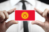 Businessman holding a business card with Kyrgyzstan Flag — Stock Photo