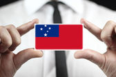 Businessman holding a business card with Samoa Flag — Stock Photo