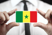 Businessman holding a business card with Senegal Flag — Stock Photo