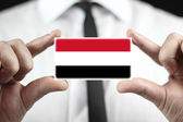 Businessman holding a business card with Yemen Flag — Stock Photo
