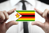 Businessman holding a business card with Zimbabwe Flag — Stock Photo