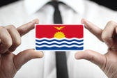 Businessman holding a business card with Kiribati Flag — Stock Photo