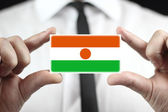Businessman holding a business card with Niger Flag — Stock Photo