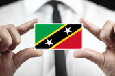 Businessman holding a business card with Saint Kitts and Nevis Flag — Stock Photo