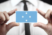 Businessman holding a business card with Micronesia Flag — Стоковое фото