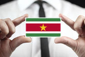 Businessman holding a business card with Suriname Flag — Stock Photo