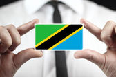 Businessman holding a business card with Tanzania Flag — Stock Photo
