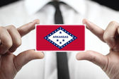 Businessman holding a business card with Arkansas State Flag — Stock Photo