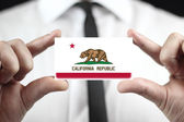 Businessman holding a business card with California State Flag — Foto Stock