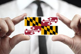 Businessman holding a business card with Maryland State Flag — Стоковое фото