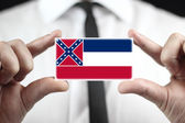 Businessman holding a business card with Mississippi State Flag — Стоковое фото