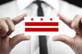Businessman holding a business card with Washington DC Flag — Stock Photo