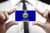 Businessman holding a business card with Kansas State Flag — Foto Stock