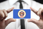 Businessman holding a business card with Minnesota State Flag — Стоковое фото