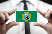 Businessman holding a business card with Washington State Flag — Stock Photo