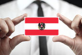 Businessman holding a business card with Austria Flag — Stock Photo