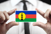 Businessman holding a business card with New Caledonia Flag — Stock Photo