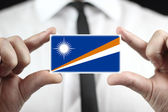Businessman holding a business card with Marshall Islands Flag — Stock Photo