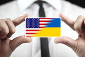 Businessman holding a business card with Ukraine and USA Flag — Stock Photo