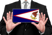 Businessman holding a business card with American Samoa Flag — Stock Photo