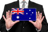 Businessman holding a business card with Australia Flag — Stock fotografie